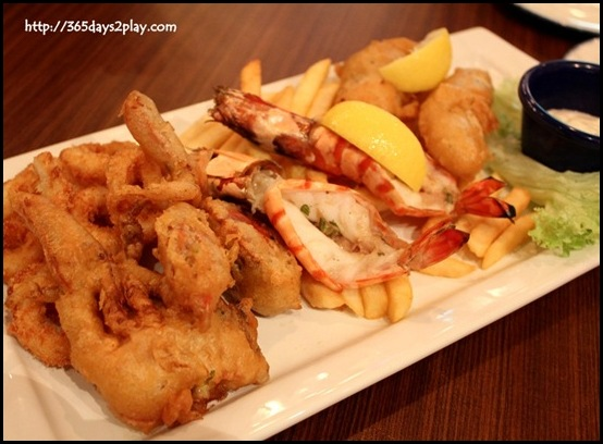 Hard Rock Cafe - Seafood Platter with an assortment of grilled prawns, calamari rings, battered sea bass fillet, soft shell crab served on a bed of french fries with tartar sauce $28   (2)