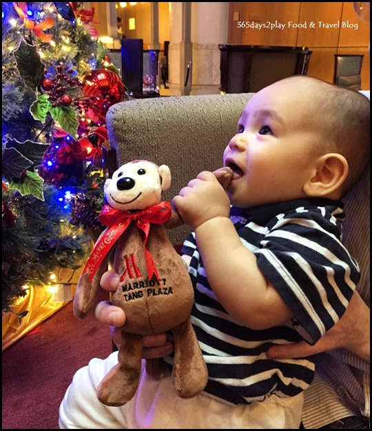 Baby holding soft toy looking at Christmas decorations