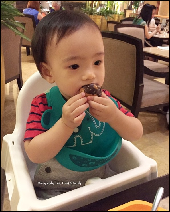 Toddler stuffing face with chocolate eclair